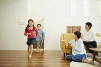 リビングルームで走り回る子供達とくつろぐ両親