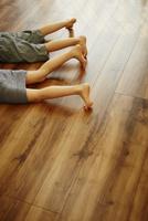フローリングの床に寝転んだ子供達の足
