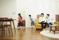 リビングルームで走り回る子供達とソファに座る両親