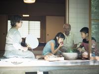 縁側で冷えた野菜を食べる孫たちと祖父母