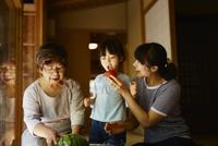 女の子にトマトを食べさせる母親とスイカを冷やす祖母