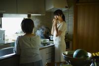 キッチンで枝豆を食べる娘と母親