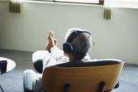 ヘッドフォンで音楽を聴くシニア男性
