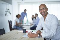 仕事をする外国人男性とミーティングをする同僚たち