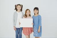 メッセージボードを持つ日本人と外国人の女の子3人