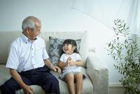 ソファに座る女の子と祖父