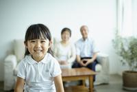 笑顔の女の子とソファに座る祖父母