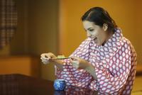和菓子を見て喜ぶ浴衣姿の外国人女性