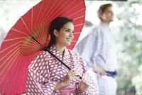 和傘をさす外国人女性と外国人男性
