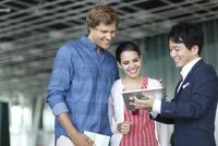 外国人カップルと旅行代理店の日本人男性スタッフ