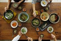 和食がのった食卓と食事をする4人の手元