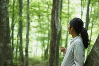森の中で音楽を聴く女性