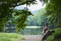 水辺の岩の上に座る女性