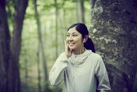 木にもたれて音楽を聴く女性 11070024675| 写真素材・ストックフォト・画像・イラスト素材|アマナイメージズ