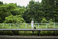 駅のホームに立つ女性