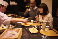 寿司屋で食事をする外国人カップル