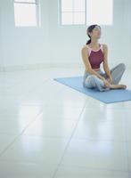 フィットネス姿で床に座る女性