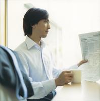 英字新聞を読む出勤前のビジネスマン 11070025983| 写真素材・ストックフォト・画像・イラスト素材|アマナイメージズ