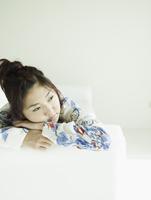 ソファに横になりくつろぐ若者女性 11070026185  写真素材・ストックフォト・画像・イラスト素材 アマナイメージズ