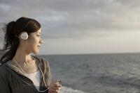 海辺で音楽を聴く女性