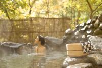 桶と手ぬぐいと紅葉と露天風呂に入る女性