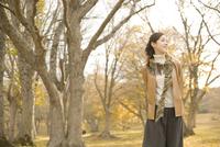 紅葉の森林とマフラーを巻いた女性