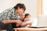 パソコンの画面を見つめる赤ちゃんと若い夫婦
