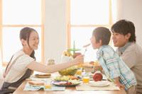 息子にウィンナーを食べさせる母親と見守る父親