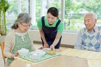 介護施設でシニア女性に食事を配膳する女性介護士 11071000585| 写真素材・ストックフォト・画像・イラスト素材|アマナイメージズ