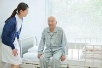 ベッドに座るシニア男性と看護師
