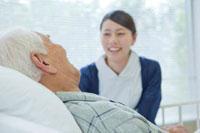 ベッドで横になるシニア男性と笑顔で話す看護師 11071000601| 写真素材・ストックフォト・画像・イラスト素材|アマナイメージズ