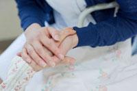 ベッドで横になるシニア女性の手を握る看護師
