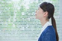 窓際で空を見上げる看護師の横顔
