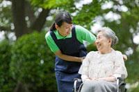 シニア女性の乗った車いすを押す女性介護士