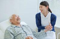 ベッドで横になるシニア男性と笑顔で話す看護師