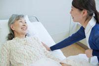 ベッドで看護師と笑顔で会話するシニア女性