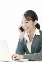 ノートパソコンを見ながら携帯電話で話すスーツ姿の女性