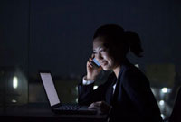 暗闇で携帯電話で話すスーツ姿の女性