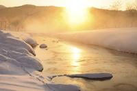 日の出と朝霧の清流雪景色