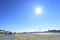 荒川土手と東京スカイツリーに太陽