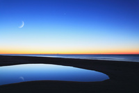 朝焼けの海と月