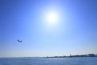 東京港より飛行機と太陽 11076015181| 写真素材・ストックフォト・画像・イラスト素材|アマナイメージズ