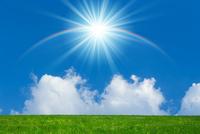 緑の草原に太陽と虹