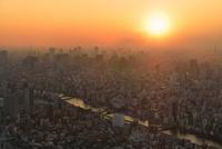 東京スカイツリーより靄かかるビル群と夕日に隅田川