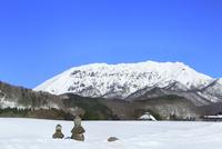 雪の大山と茅葺き小屋ある田園風景