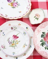 Floral patterned porcelain plates on checked table cloth