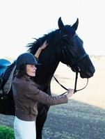 Woman standing by horse holding reins 11077000973| 写真素材・ストックフォト・画像・イラスト素材|アマナイメージズ