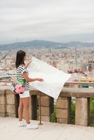 Woman reading map overlooking city