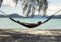 Woman in a hammock on the beach, Malaysia.