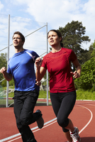Woman and man jogging on running track